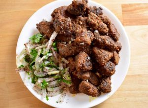 fried cubes of liver on a plate with a raw onion and parsley salad