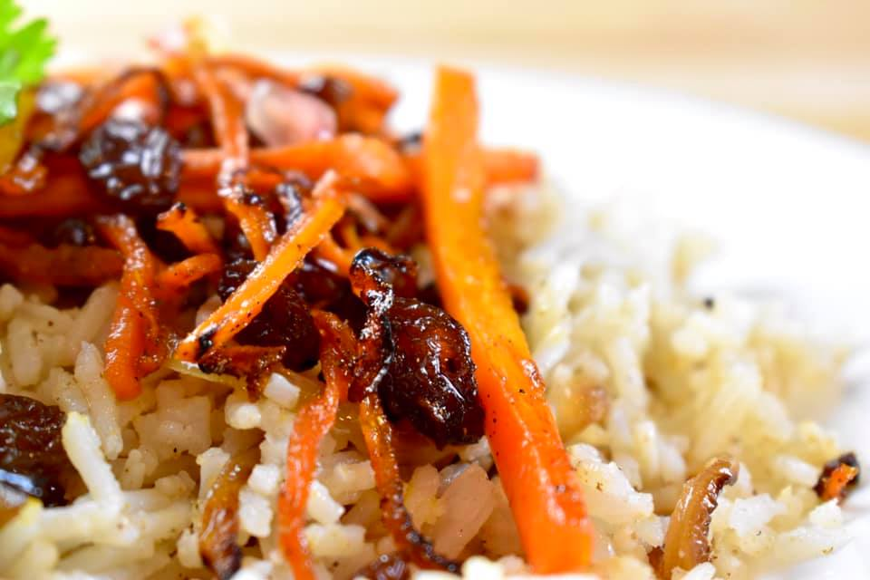 rice pilaf with sauteed carrots and raisins on top