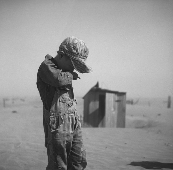 A young boy covers his mouth during a dust storm on farm. Cimarron County, Oklahoma. April 1936. Credits: Arthur Rothstein; The Library of Congress, Prints & Photographs Division