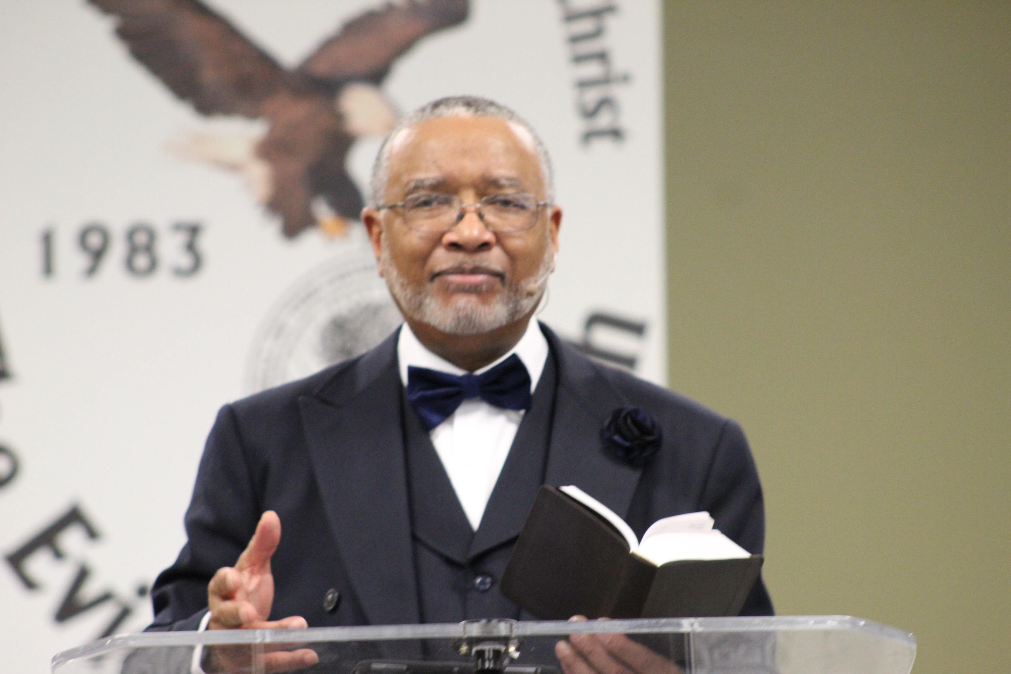 Dr. Gary L. Cordon, Sr. preaching holding Bible in left hand in front of logo in pulpit.