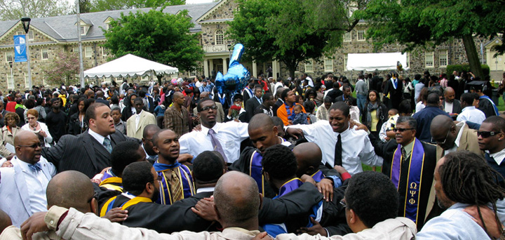 Cheyney University of Pennsylvania graduates embracing on the campus courtyard.