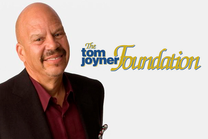 The Tom Joyner Foundation's Tom Joyner smiling in a suit standing next the organization logo.