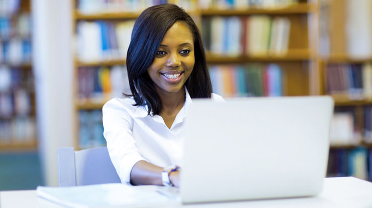 African American senior submits her college application online at the school library.