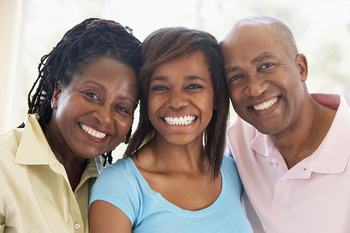 Female college student smiling with parents at home for Holiday break