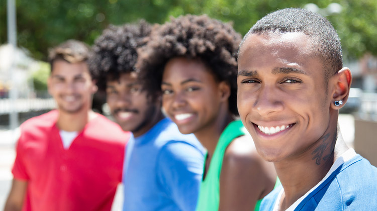 Avoiding the Freshman 15: A group of African American and Latino college students laughing at camera on campus.