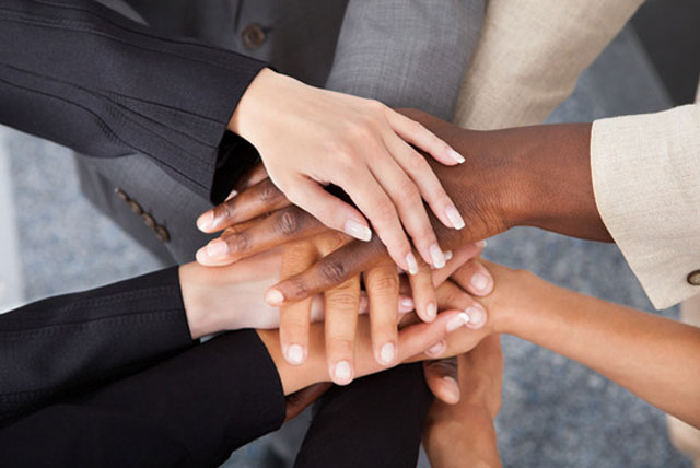 Multiracial businesspeople stacking hands.