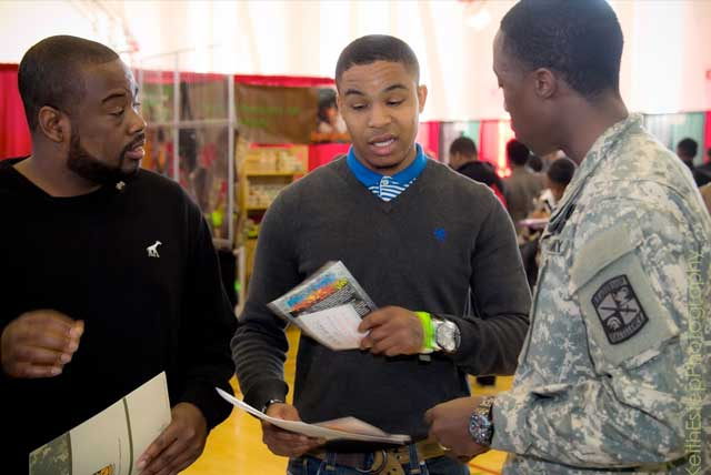 Black College Expo attendee talks with military recruiter at about college options after high school.