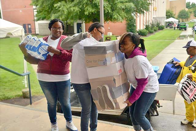 Incoming freshmen girls struggle to bring several boxes of shoes up stairs at the entrance of their dorm at North Carolina A&T State University.