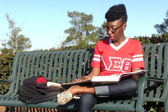 Delta Sigma Theta member T'Edra Jackson studies outside on the campus of Paul Quinn College.