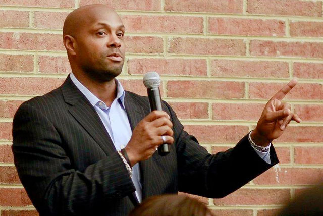 Chris Cathcart pictured holding a microphone speaking in front of an audience on fundraising party ideas for HBCU groups.