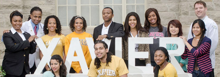 Xavier University of Louisiana students stand in front of school signage.