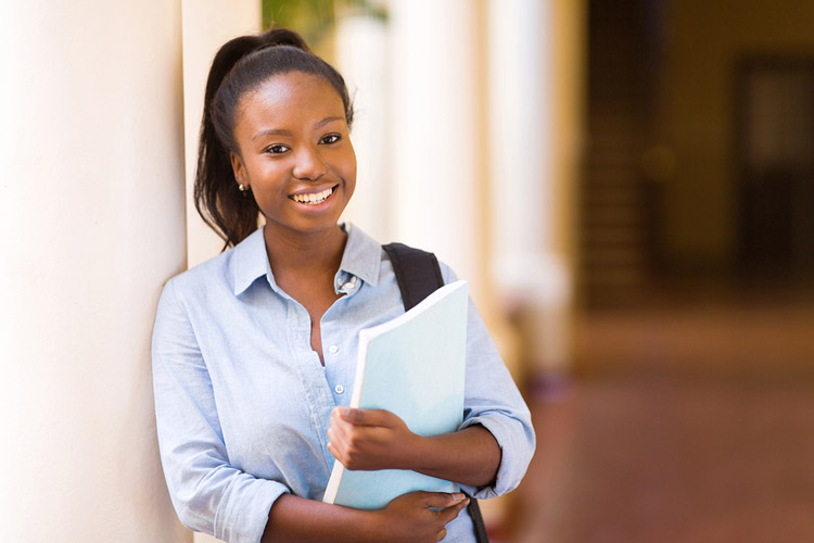 A Black female first generation college student poses on campus holding her books.