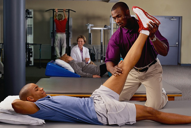 Doctor of Physical Therapy: Therapist helps patient stretch out leg on the floor in a session.