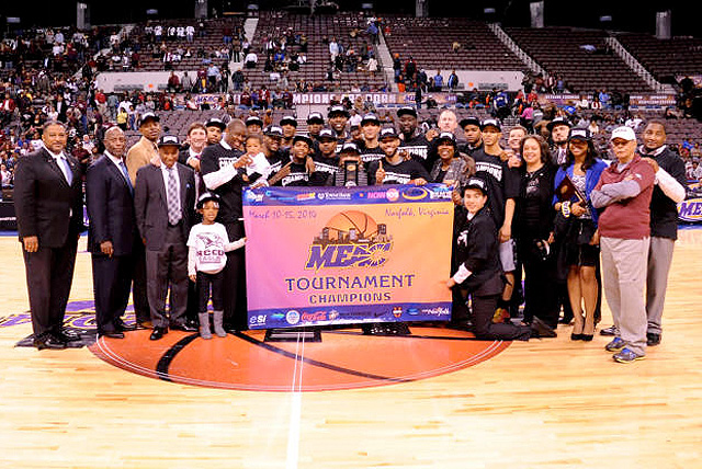 2014 MEAC Tournament champions North Carolina Central pose at center court behind championship banner with coaching staff.