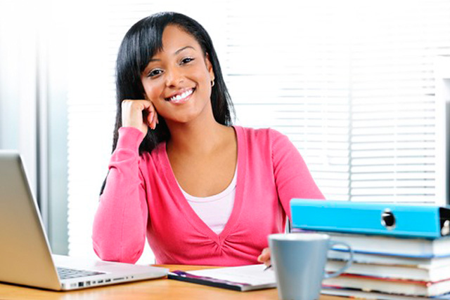 Happy female college student working on research paper topics.