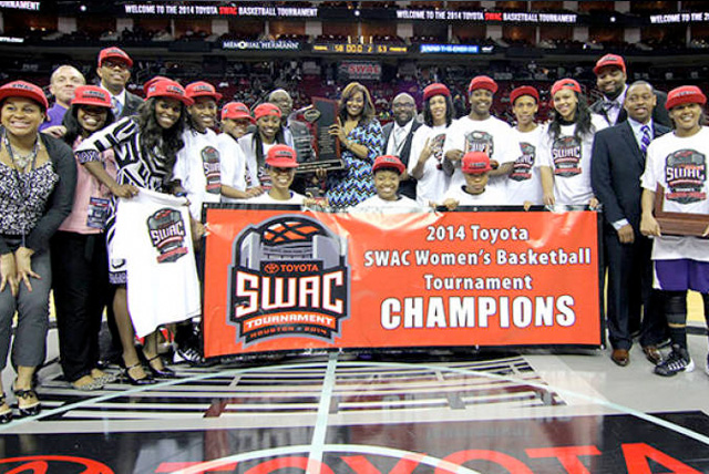 2014 SWAC Tournament women's basketball champions Prairie View A&M pose at center court behind championship banner with coaching staff.