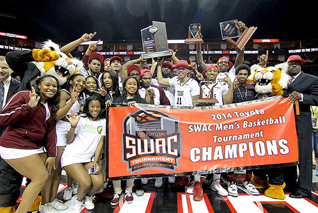 2014 SWAC Tournament champions Texas Southern pose at center court behind championship banner with coaching staff.
