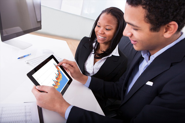 Two African-American students looking at economics data on tablet for pre-doctoral fellowship research.
