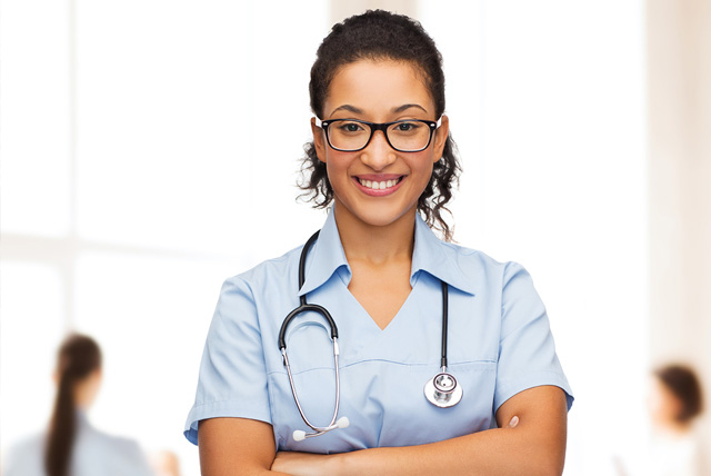 Tylenol Scholarship: Smiling female african American doctor or nurse in eyeglasses with stethoscope.