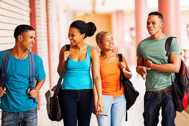 Class of 2018: Group of cheerful HBCU freshmen walking in building corridor.