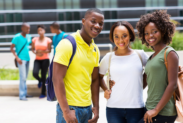 A group of smiling African American students pose during their HBCU campus visit.