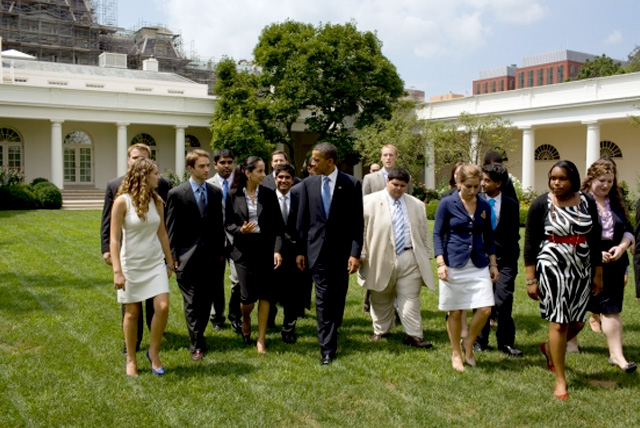 A group of White House summer interns walk with the President in the Rose Garden.