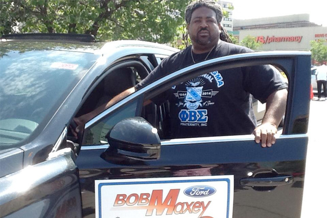 A Phi Beta Sigma Fraternity member poses with a Lincoln Motors vehicle at the 2014 Divine Nine Driven To Give Program event in Detroit, MI on Aug. 16th.