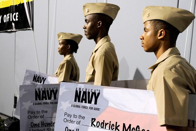 Three students holding big paper checks receive NROTC scholarships.