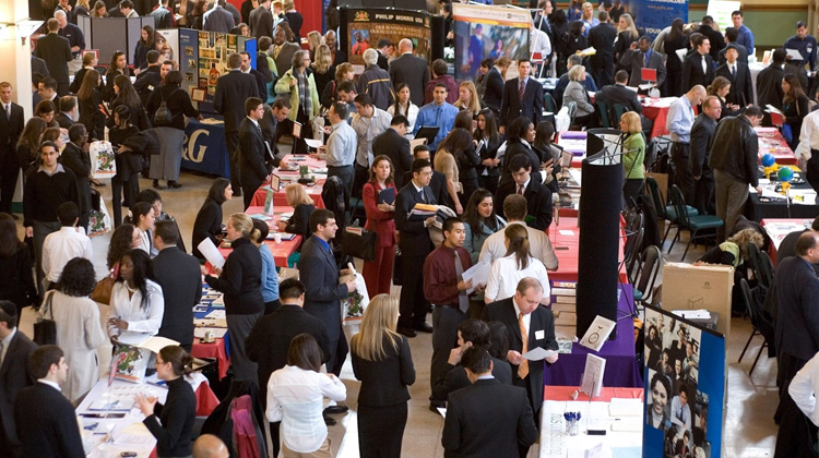 College bound High School students speak with various college representatives at an NACAC college fair.