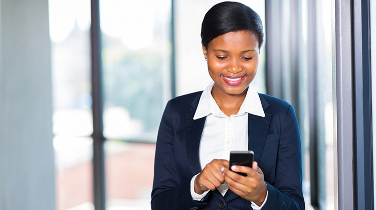 Smiling African-American law student using legal app on her smart phone.