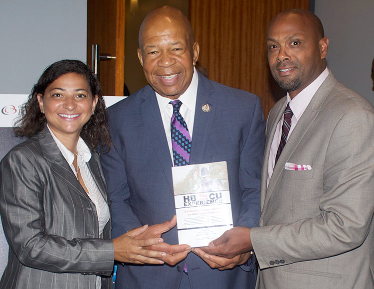 HBCU Experience Book Editors stand Congressman Elijah Cummings holding up a copy of the book.