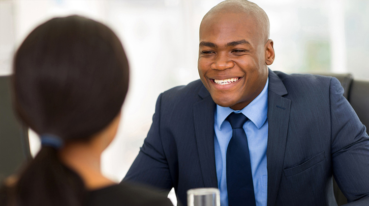 A young African-American male smiles in a job interview with potential employer.