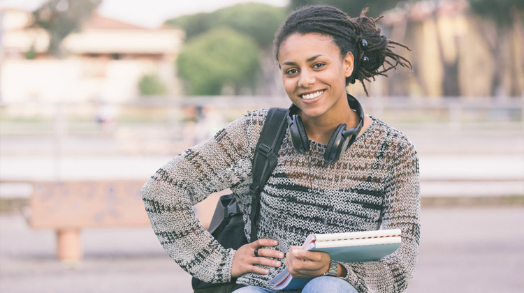African-American female high school student sits outside with her books, headphones and backpack.