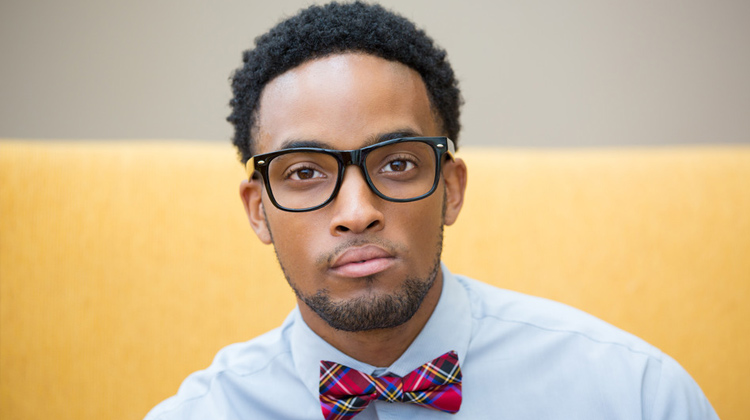 A close up portrait black male college student with black glasses and bow tie, isolated yellow white background.