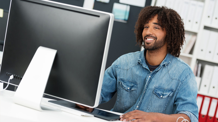 Friendly young African American businessman in a casual denim shirt sitting at his desktop computer in the office smiling