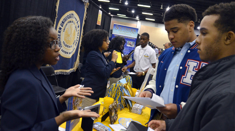A representative at the Southern University and A&M College booth speaks with high schools students at the 2015 Atlanta Black College Expo.