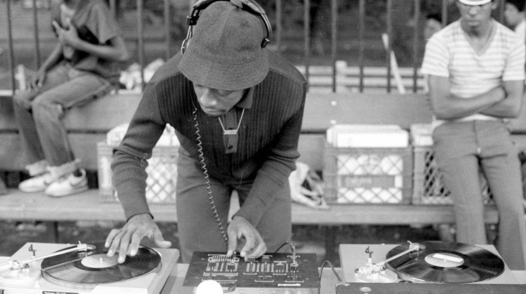 Hip-hop studies: Vintage image of old school Hip-Hop DJ, who is mixing and scratching on two turn tables.