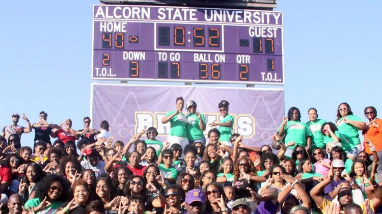 Members of the Divine Nine Black Greek Organizations pose together under Alcorn State's Spinks-Casem Stadium scoreboard.