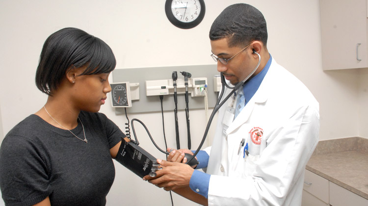 Student Health Services staff checks the blood pressure of a student during an office visit.