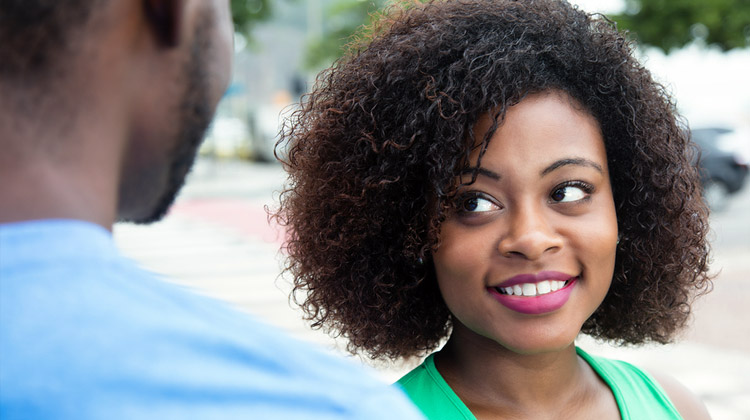 African American female college student talking to a male friends on the campus of an HBCU.