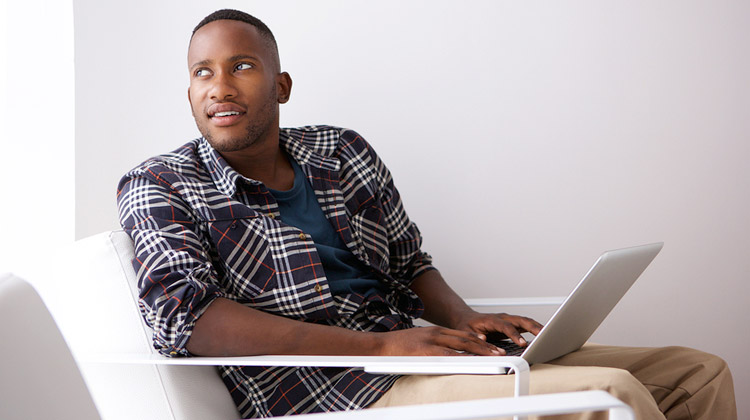 Before email your professor: A relaxed young black college student is sitting on a chair with a laptop, looking away and thinking of what to type.