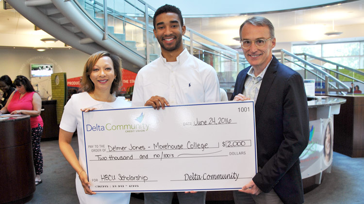 Delmer Jones III holds a giant scholarship check with KISS 104 radio personality Veronica Waters and Delta Community Credit Union C.O.O. Matthew Shepherd