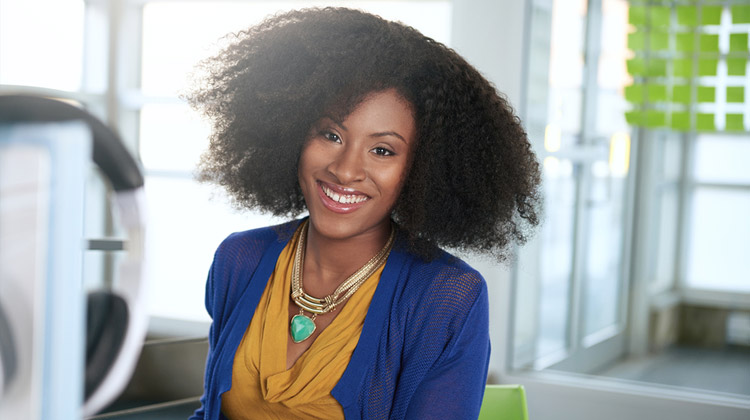 A friendly African American HBCU college student at her work study job on campus.