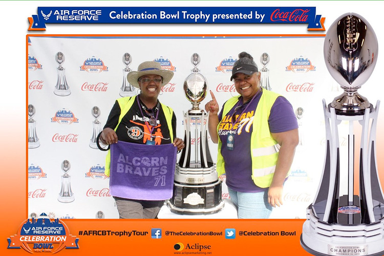 Alcorn State University fans pose with the Celebration Bowl Trophy during the AFRCB trophy tour at the 2016 MEAC/SWAC Challenge.