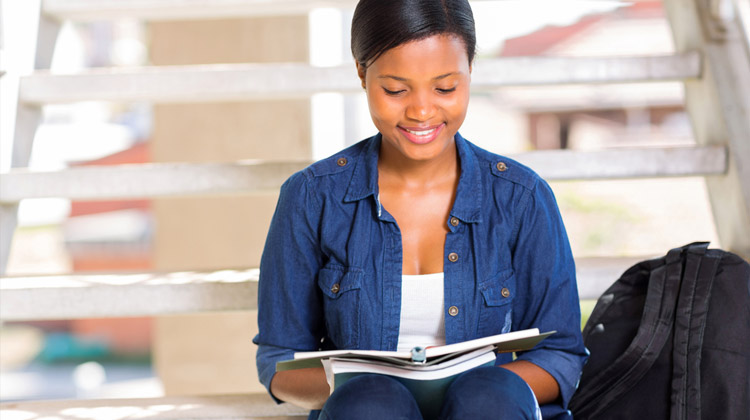 African-American university student is reading notes from her STEM courses.