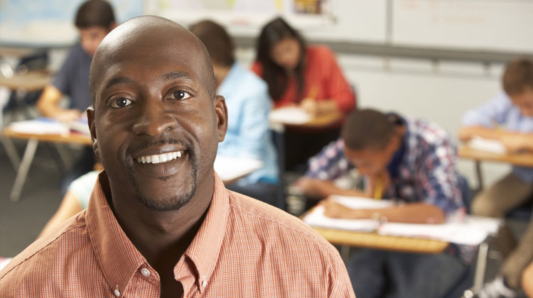 Education programs: Portrait of a Black male teacher in a classroom.