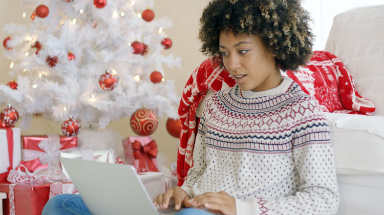 An HBCU student updates her resume and LinkedIn profile in between surfing the web during Holiday Break in front of the tree.