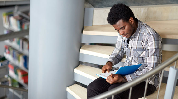 African American student reading college text book at library to improve his grades.