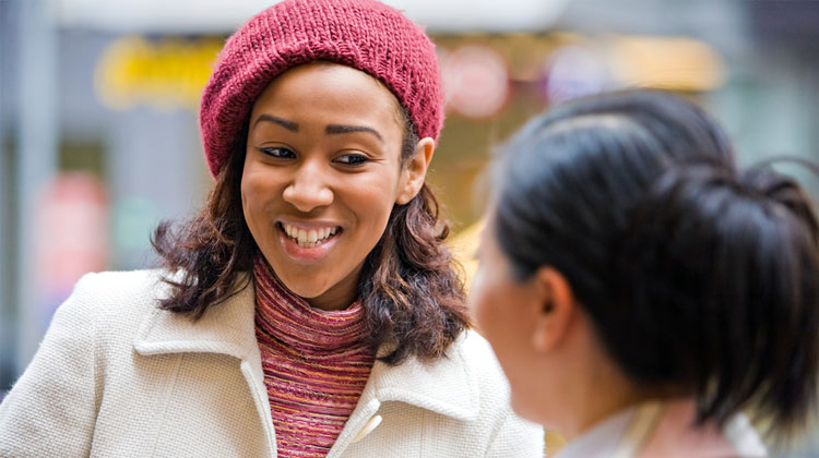 A smiling HBCU female business student is having a casual discussion with her mentor during a lunch meeting in the city.