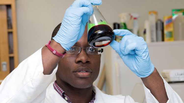 A Florida A&M University student researcher hold a beaker up to the light in a laboratory.
